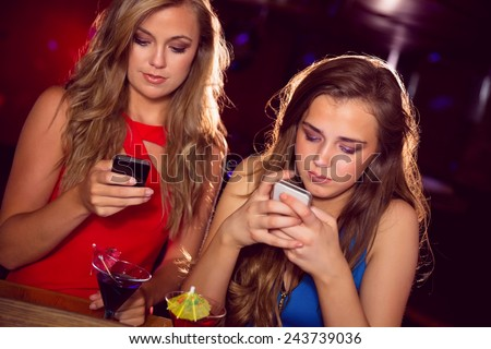 Pretty friends looking at smartphones at the nightclub - stock photo