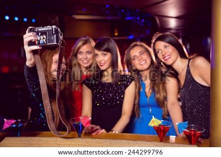 Pretty friends taking a selfie at the nightclub - stock photo