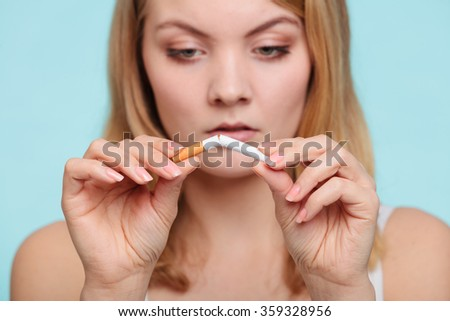 Pretty girl breaking up with cigarette. Addicted nicotine problems in young age. Quitting from addiction concept. - stock photo