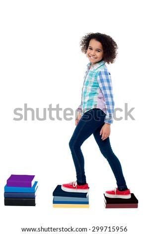 Pretty girl child climbing on notebooks over white - stock photo