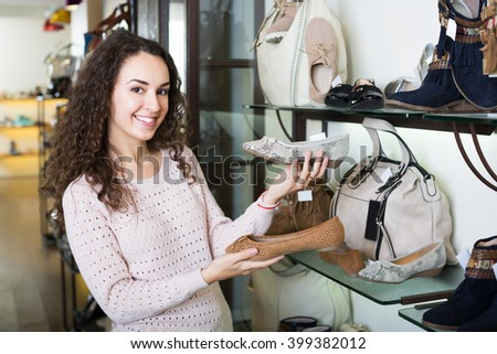 Pretty girl chooses summer shoes at fashionable shop