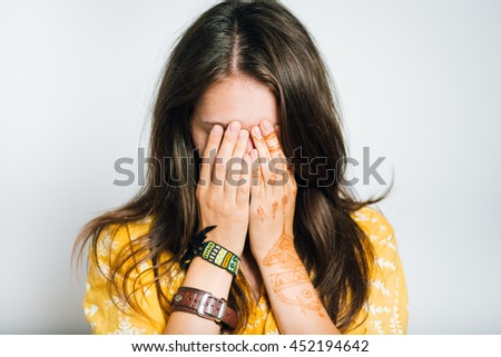 pretty girl closes eyes with hands, studio photo, isolated