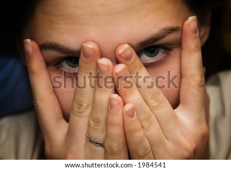 Pretty girl covering her face, looking through fingers - stock photo