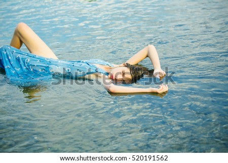 Pretty girl cute beautiful woman in blue dress lies outdoors in water on natural background