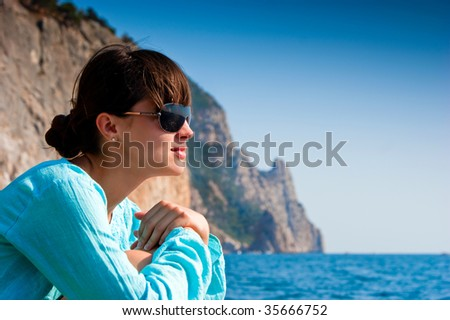 Pretty girl dreaming and looking at the ocean - stock photo