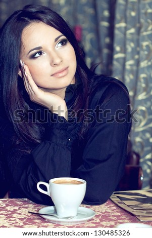 Pretty girl drinking coffee or tea and thinking - stock photo