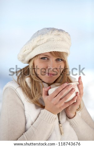 pretty girl drinking tea by wintry day - stock photo