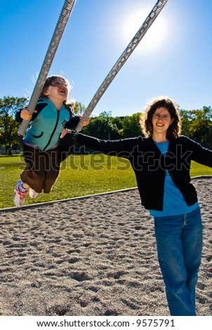 pretty girl enjoys swinging while her mother pushes her during a clear sunny day - stock photo