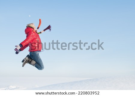 Pretty girl enjoys winter. Happy girl jumps up on the field in sunny winter day. - stock photo