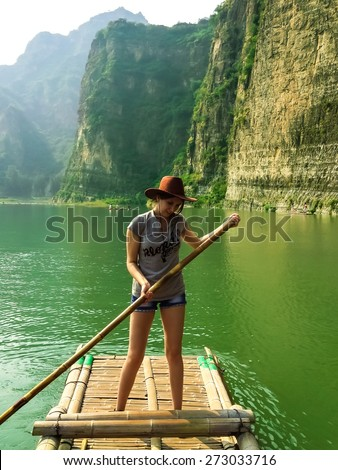 Pretty girl floating on a bamboo raft on the green water of lake, Shidu, China. Shidu conservation area is one of the most beautiful places with unique nature in China. - stock photo