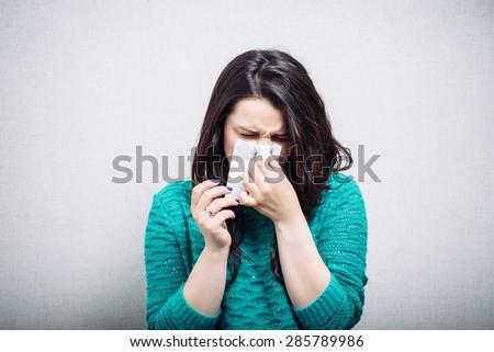 Pretty girl has a runny nose - stock photo