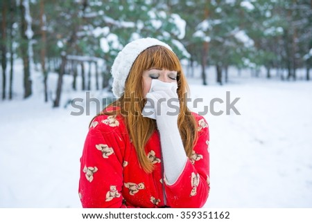 Pretty girl has flu and fever in winter day outdoor. redhead wipes snot handkerchief. Women with tissue having flu or allergy - stock photo