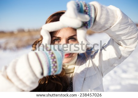 Pretty girl having fun outdoor, making frame with hands, taking picture with imaginary camera, winter time - stock photo