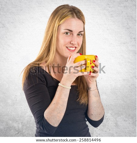 Pretty girl holding a cup of coffee over textured background