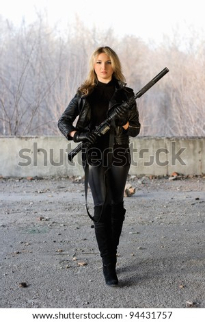 Pretty girl holding a gun in neglected building - stock photo