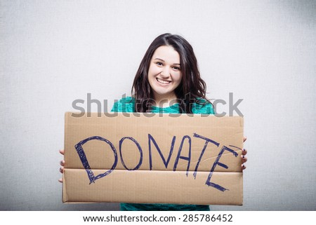 Pretty girl holding a sign donate - stock photo