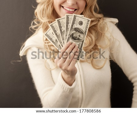 Pretty girl holding 500 dollars and smiling - stock photo
