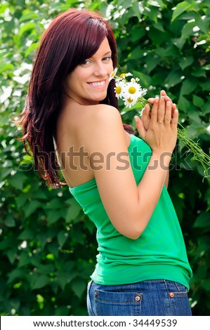 Pretty Girl Holding Flowers In The Summer Sun - stock photo