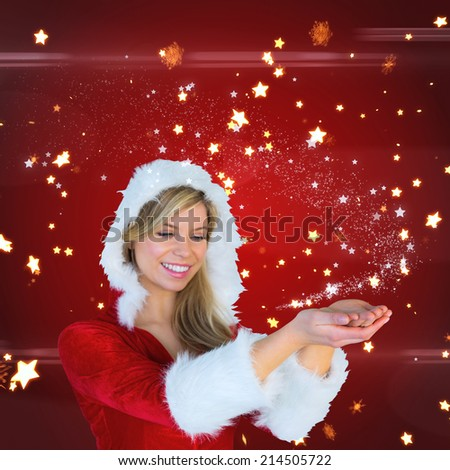 Pretty girl holding hands out in santa outfit against bright star pattern on red