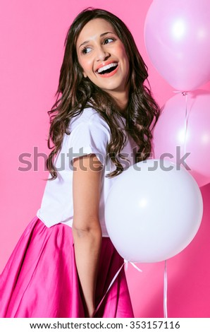 Pretty girl holding pink and white balloons on pink background, playful cute party celebration