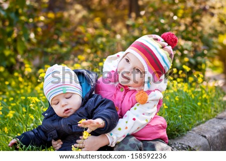 Pretty girl hugging baby brother outdoors in spring  - stock photo