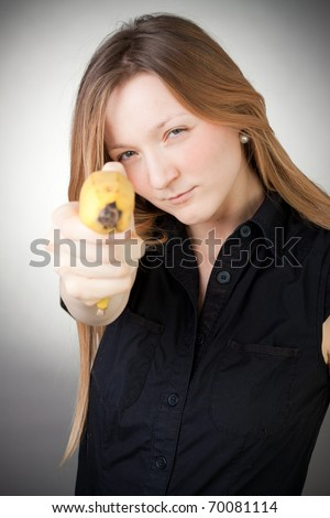 Pretty girl in a black dress is holding a banana as a gun, with grey background - stock photo
