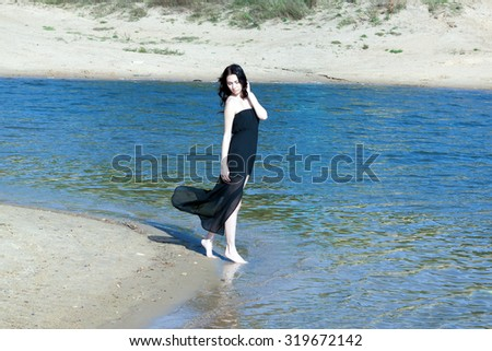 pretty girl in a long dress posing standing on the beach
