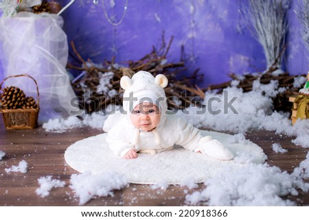 pretty girl in a New Year's bear suit near a Christmas tree. blue accent decor - stock photo
