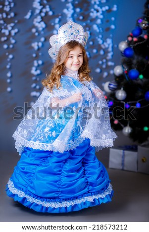 pretty girl in a New Year's suit near a Christmas tree. blue accent decor - stock photo