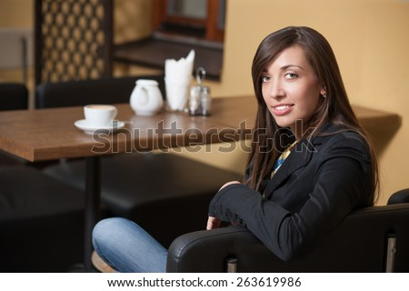Pretty girl in cafeteria? Young beautiful girl posing across table with cup of coffee - stock photo