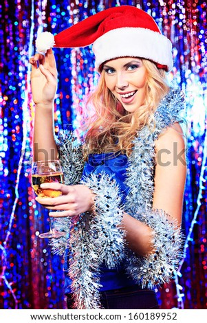 Pretty girl in Christmas clothes on a party. Disco lights in the background.