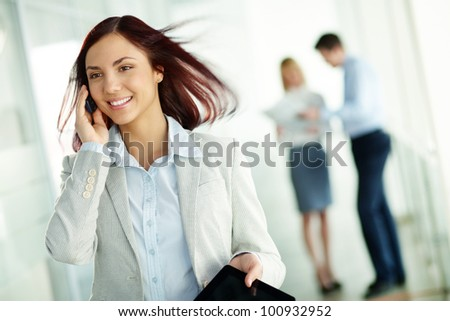 Pretty girl in formal wear talking on her mobile phone, her colleagues holding a discussion in the background