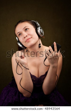Pretty girl in funky purple outfit on green background with personal audio device - stock photo