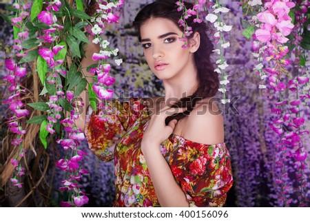 Pretty girl in garden with purple wistaria flowers - stock photo