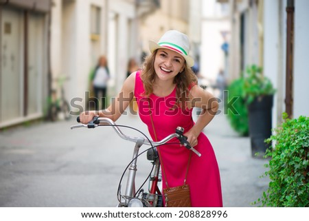 Pretty girl in hat and pink dress riding a bicycle at Italian streets - stock photo