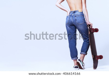 pretty girl in jeans with skateboard on white background. isolated. view from back. - stock photo