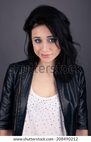 pretty girl in leather jacket with piercings smiling on gray background