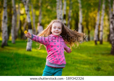 Pretty girl in park.   girl running in the park. Wind blows hair.   - stock photo