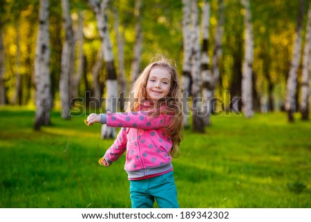 Pretty girl in park. Happy girl running in the park. Wind blows hair.   smile, summer - stock photo