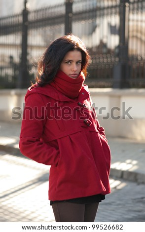 Pretty girl in red overcoat on the street - stock photo