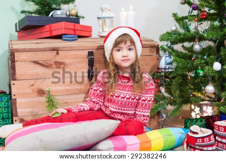 Pretty girl in Santa hat waiting Christmas eve while sitting next to green tree at home - stock photo