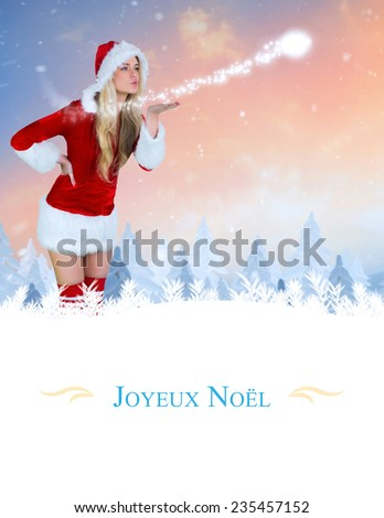 pretty girl in santa outfit blowing against border - stock photo