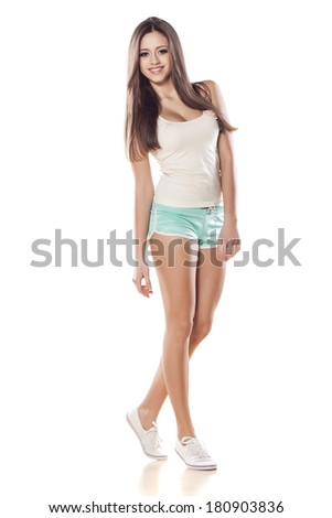 pretty girl in shorts and shirt posing on white