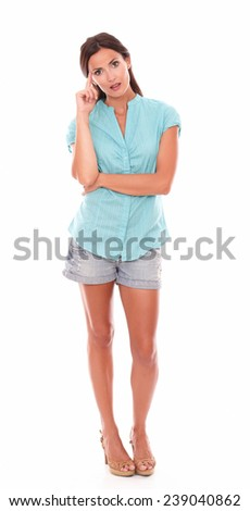Pretty girl in shorts jeans standing full length and wondering about a question in white background - copyspace - stock photo