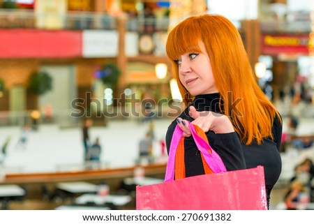 pretty girl in the mall with colorful bags - stock photo