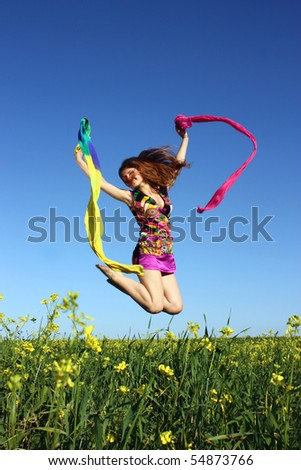 Pretty girl in the summer  jumping on the field with a scarf