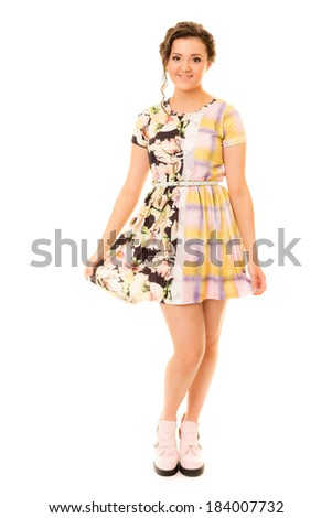 Pretty girl in two-sided dress and pink shoes against a white ba