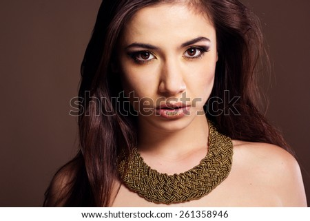 Pretty girl is wearing golden bijouterie. Fashion photo. Beauty and style - stock photo