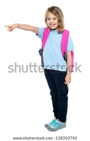 Pretty girl kid in casuals pointing away isolated on white. - stock photo