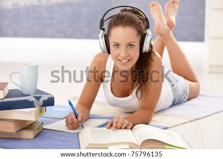 Pretty girl learning at home laying on floor, using headphones, smiling.? - stock photo
